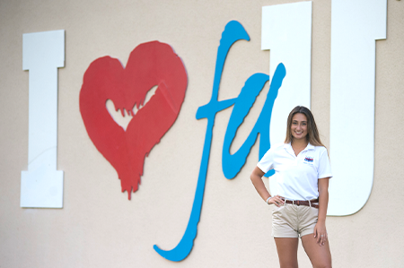 Female standing next to wall that reads 'I Love FAU'